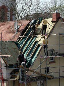 Zimmermänner bringen eine Zwischensparrendämmung an, im Rahmen einer Dachsanierung.