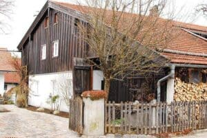 Ein Wohnhaus mit angebauter Scheune. Verbunden sind beide Bauten mit einem Schleppdach.