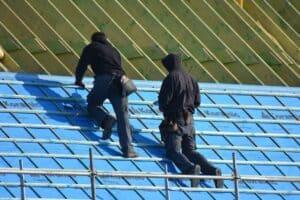 Dachdecker bringen eine Aufsparrendämmung an