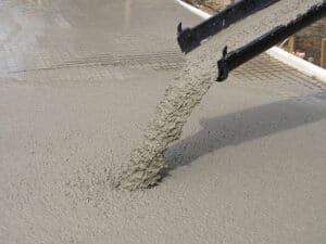 Maschinell angemischter Beton wird auf der Baustelle als Bodenplatte gegossen.