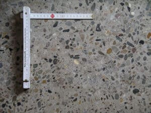 Querschnitt durch normalen Beton. Gut zu sehen sind die Kies-Steinchen die hier mitgemischt wurden.