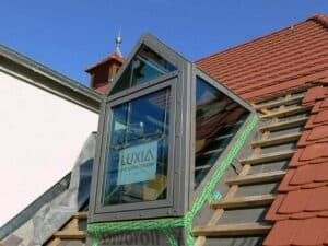 Eine frisch eingebaute Gaube. Rings um die Gaube muss das Dach wieder gedeckt werden.